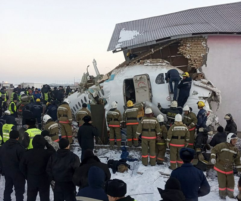 In this handout photo provided by the Emergency Situations Ministry of the Republic of Kazakhstan, police and rescuers work on the site of a plane crash near Almaty International Airport, outside Almaty, Kazakhstan, Friday, Dec. 27, 2019. Almaty International Airport said a Bek Air plane crashed Friday in Kazakhstan shortly after takeoff causing numerous deaths. The aircraft had 100 passengers and crew onboard when hit a concrete fence and a two-story building shortly after takeoff. ( Emergency Situations Ministry of the Republic of Kazakhstan photo via AP)