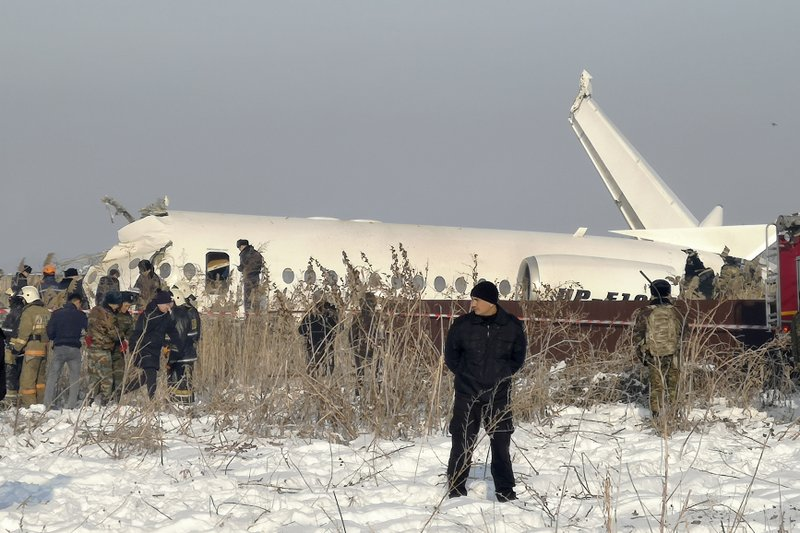 Police guard as rescuers work on the side of a plane crashed near Almaty International Airport, outside Almaty, Kazakhstan, Friday, Dec. 27, 2019. The Kazakhstan plane with 100 people aboard crashed shortly after takeoff early Friday. (AP Photo/Vladimir Tretyakov)