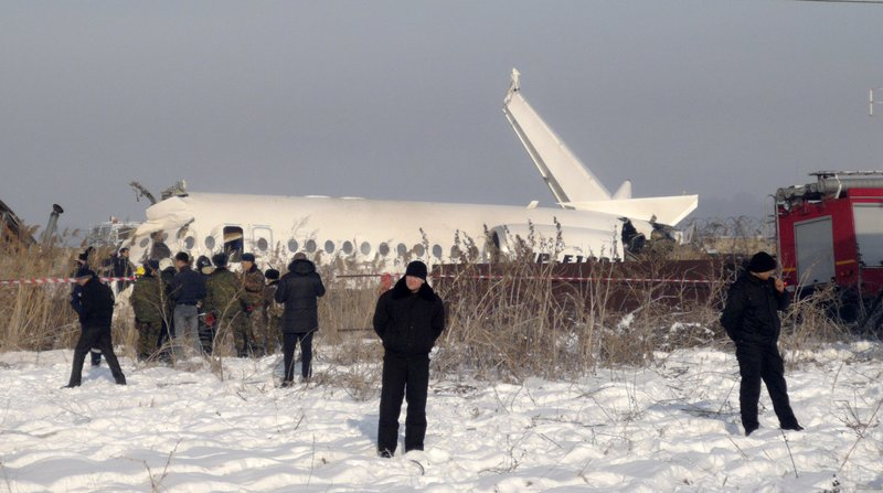 Police stand guard as rescuers assist on the site of a plane crash near Almaty International Airport, outside Almaty, Kazakhstan, Friday, Dec. 27, 2019. Almaty International Airport said the Bek Air plane crashed Friday in Kazakhstan shortly after takeoff causing numerous deaths. The aircraft had 100 passengers and crew onboard when hit a concrete fence and a two-story building shortly after takeoff. (AP Photo/Vladimir Tretyakov)