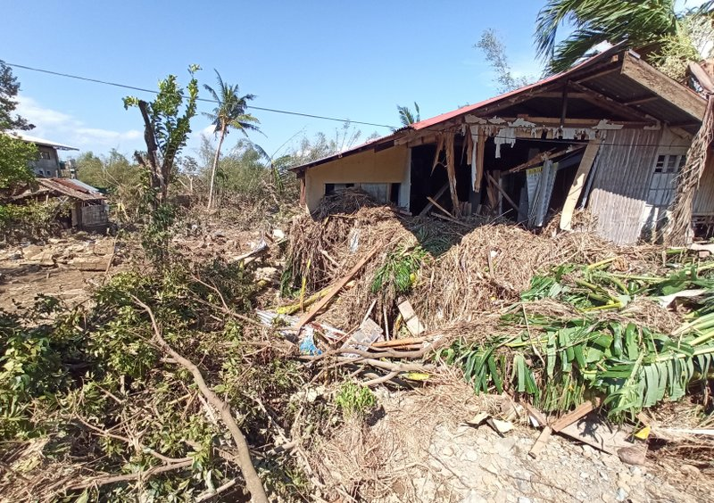Debris from floods caused by Typhoon Phanfone surround a damaged house in Balasan Town, Iloilo province, central Philippines on Thursday Dec. 26, 2019. A strong typhoon that barreled through the central Philippines left at least 20 people dead and forced thousands to flee their homes, devastating Christmas celebrations in the predominantly Catholic country. (AP Photo/Leo Solinap)