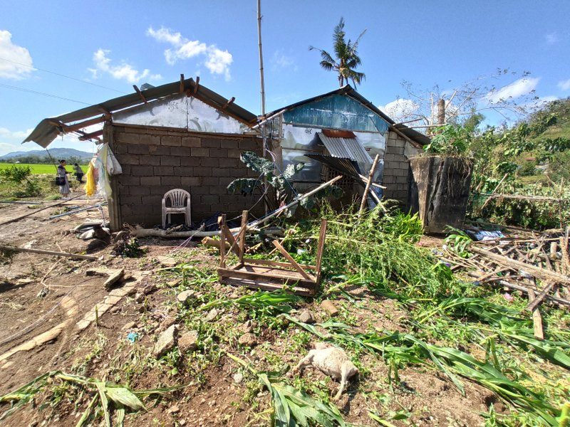 People walk beside homes damaged by Typhoon Phanfone at Batad Town, Iloilo province, central Philippines on Thursday Dec. 26, 2019. A strong typhoon that barreled through the central Philippines left at least 20 people dead and forced thousands to flee their homes, devastating Christmas celebrations in the predominantly Catholic country. (AP Photo/Leo Solinap)