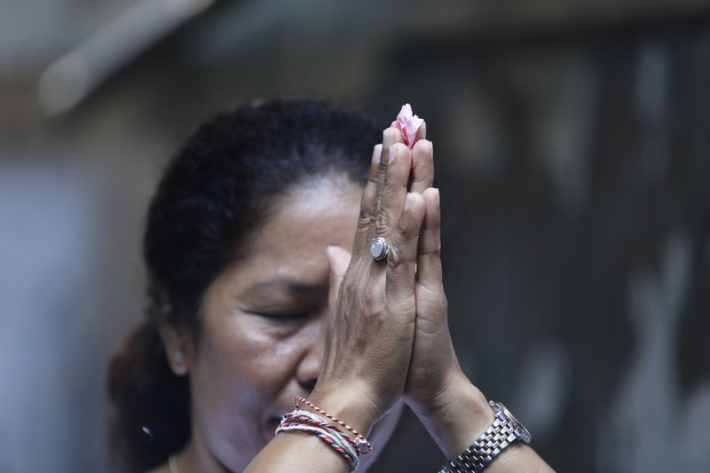 Ni Luh Erniati prays at a temple in her home in Bali, Indonesia on Friday, April 26, 2019. Erniati's husband, Gede Badrawan, was killed in the 2002 Bali bombings. She has since reconciled with a former bombmaker whose brothers helped orchestrate the Bali attack as part of a peacebuilding program bringing together ex-terrorists and victims. (AP Photo/Firdia Lisnawati)