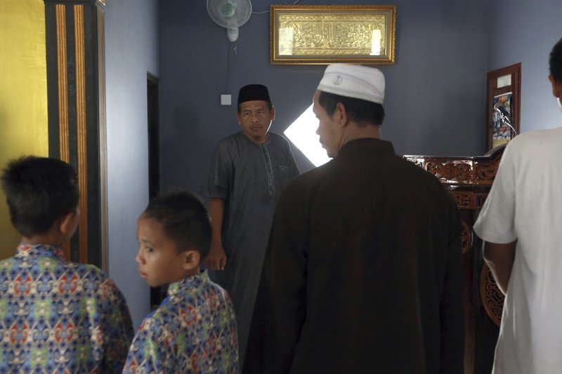 Ali Fauzi, center, prepares to pray at a mosque in Tenggulun, East Java, Indonesia, on Saturday, April 27, 2019. Three of Fauzi's brothers helped orchestrate the 2002 Bali bombings, and Fauzi was once the chief bombmaking instructor for Jemaah Islamiyah, the Islamic militant group behind the Bali attack. He now works with terrorism victims on peacebuilding efforts throughout Indonesia. (AP Photo/Tatan Syuflana)