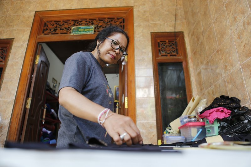 Ni Luh Erniati prepares to cut fabric to make a dress at her home in Bali, Indonesia on Thursday, April 25, 2019. After her husband was killed in the 2002 Bali bombings, the mother of two has kept her family alive by working for a small garment company an Australian man set up for Balinese bombing widows. (AP Photo/Firdia Lisnawati)