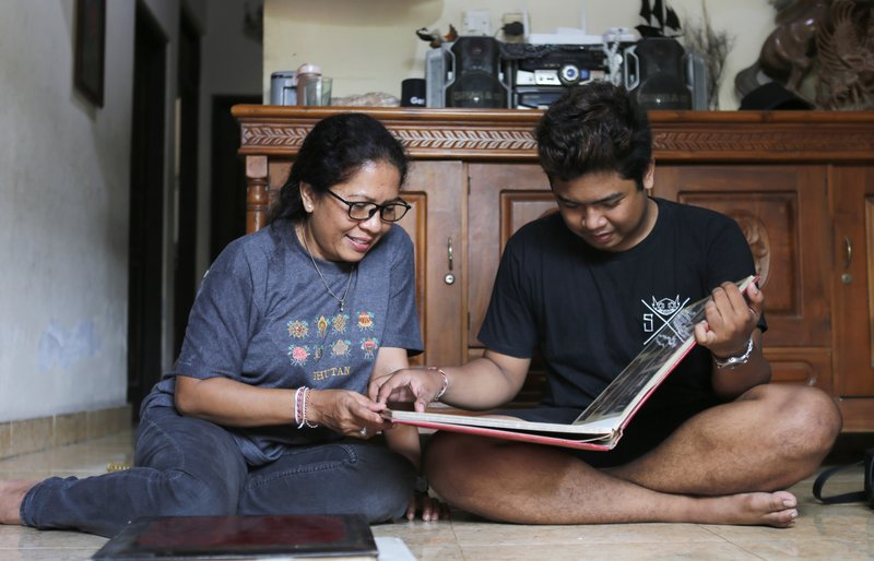 Ni Luh Erniati sits with her son, Made, going through family photo albums which show her late husband and his late father, Gede Badrawan, in Bali, Indonesia on Thursday, April 25, 2019. Gede was one of 202 people killed in the 2002 Bali bombings. After his death, the sight of Erniati's tears made Made cry, so she shut herself in the bathroom to weep alone. She spent years telling him that his father was simply away for work. He was 9 before she told him the truth. (AP Photo/Firdia Lisnawati)