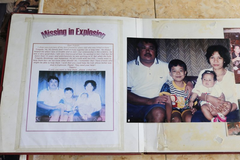 Photos of Gede Badrawan and his family are seen as Ni Luh Erniati and her son go through family albums in Bali, Indonesia on Thursday, April 25, 2019. Gede, Erniati's late husband, was one of 202 people killed in the 2002 bombings in Bali's nightclub district. (AP Photo/Firdia Lisnawati)