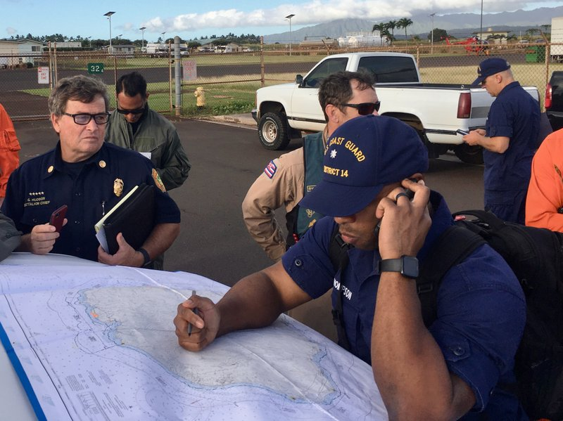 In this photo released by the U.S. Coast Guard, Coast Guard Incident Command Post responders look over a map of the Na Pali Coast State Wilderness Park on the Hawaiian island of Kauai on Friday, Dec. 27, 2019, the day after a tour helicopter disappeared with seven people aboard. Authorities say wreckage of the helicopter has been found in a mountainous area on the island. (Senior Chief Justin Shackleford/U.S. Coast Guard via AP)
