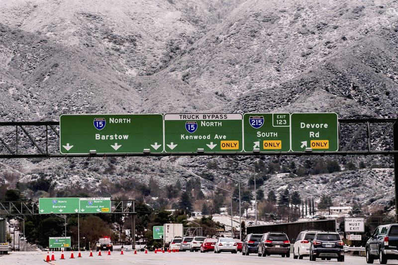 Vehicles are diverted off the northbound 15 Freeway to Kenwood Ave. on-ramp as Cajon Pass is shut down due to heavy snowfall in San Bernardino, Calif., on Thursday, Dec. 26, 2019. (Watchara Phomicinda/The Orange County Register via AP)