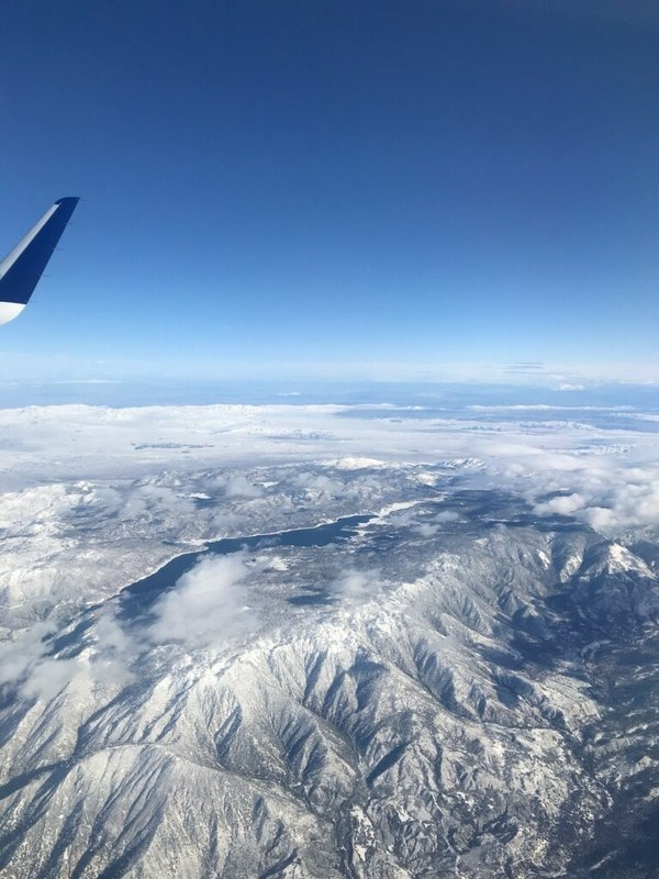 This photo provided by Greg Weber shows a snows covered Big Bear Lake in Big Bear, Calif., on Friday, Dec. 27, 2019. A winter storm has brought a deluge of rain and snow to Southern California. Snow has shut down the vital Interstate 5 in Tejon Pass through the mountains north of Los Angeles and dozens of miles of Interstate 15 from Baker, California, to Primm, Nevada. (Greg Weber via AP)