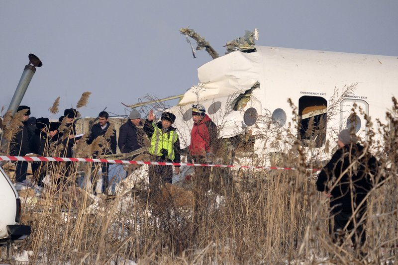 Rescuers assist on the site of a plane which crashed near Almaty International Airport, outside Almaty, Kazakhstan, Friday, Dec. 27, 2019. The Kazakhstan plane with 98 people aboard crashed shortly after takeoff early Friday. (AP Photo/Vladimir Tretyakov)