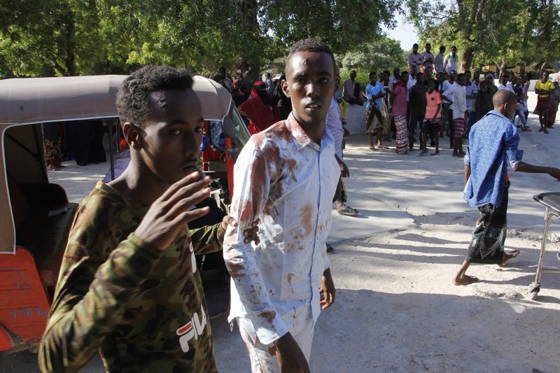 A civilian who was wounded in suicide car bomb attack is helped by a friend at check point in Mogadishu, Somalia, Saturday, Dec, 28, 2019. A police officer says a car bomb has detonated at a security checkpoint during the morning rush hour in Somalia's capital. (AP Photo/Farah Abdi Warsame)