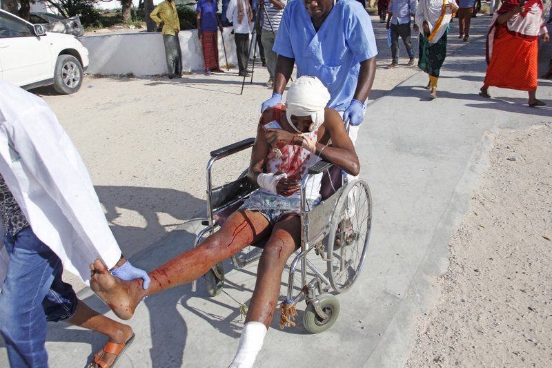 A civilian who was wounded in suicide car bomb attack is helped at check point in Mogadishu, Somalia, Saturday, Dec, 28, 2019. A police officer says a car bomb has detonated at a security checkpoint during the morning rush hour in Somalia's capital. (AP Photo/Farah Abdi Warsame)