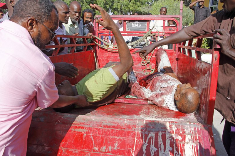 Civilians who were wounded in suicide car bomb attack are helped at check point in Mogadishu, Somalia, Saturday, Dec, 28, 2019. A police officer says a car bomb has detonated at a security checkpoint during the morning rush hour in Somalia's capital. (AP Photo/Farah Abdi Warsame)