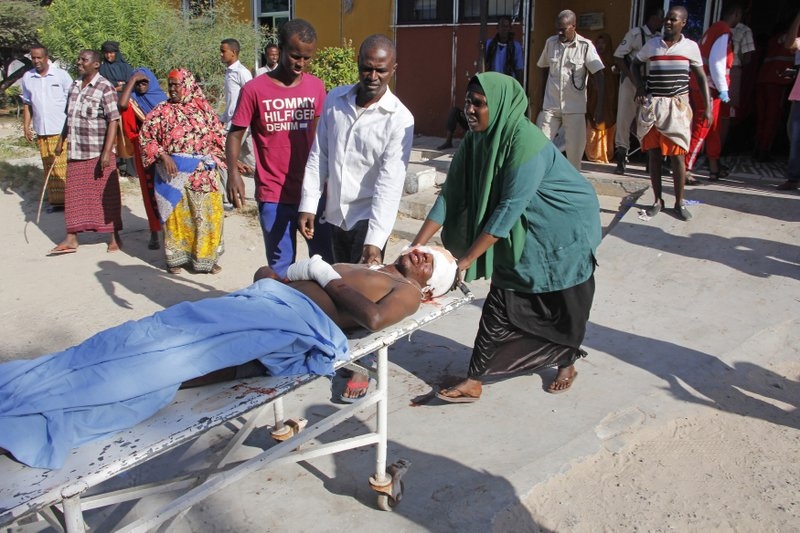 A woman helps to push a stretcher following a suicide car bomb attack at check point in Mogadishu, Somalia, Saturday, Dec, 28, 2019. A police officer says a car bomb has detonated at a security checkpoint during the morning rush hour in Somalia's capital. (AP Photo/Farah Abdi Warsame)