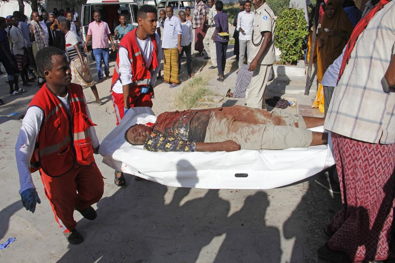 Medical personnel carry a civilian who was wounded in suicide car bomb attack at check point in Mogadishu, Somalia, Saturday, Dec, 28, 2019. A police officer says a car bomb has detonated at a security checkpoint during the morning rush hour in Somalia's capital. (AP Photo/Farah Abdi Warsame)