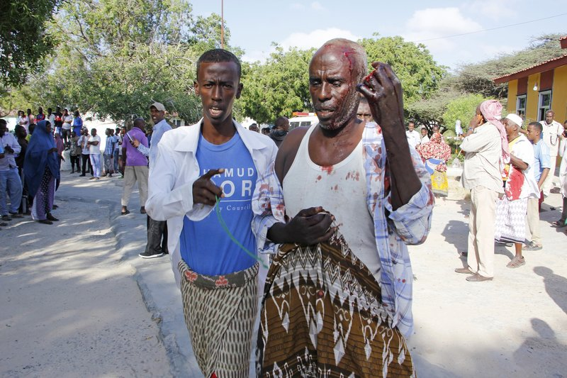 EDS NOTE GRAPHIC CONTENT - A civilian who was wounded in suicide car bomb attack is helped at check point in Mogadishu, Somalia, Saturday, Dec. 28, 2019. A police officer says a car bomb has detonated at a security checkpoint during the morning rush hour in Somalia's capital. (AP Photo/Farah Abdi Warsame)
