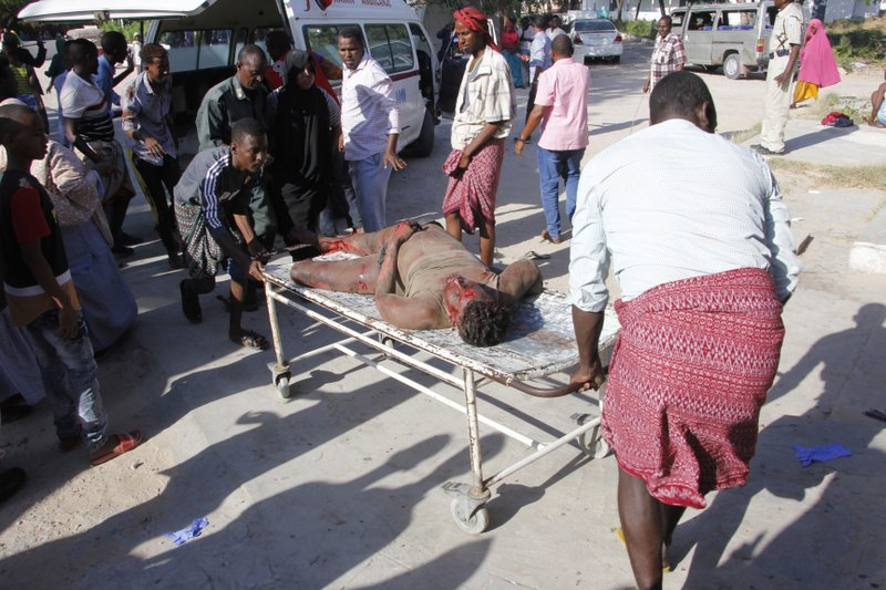 EDS NOTE GRAPHIC CONTENT - Medical personnel carry a civilian who was wounded in suicide car bomb attack at check point in Mogadishu, Somalia, Saturday, Dec, 28, 2019. A police officer says a car bomb has detonated at a security checkpoint in Somalia's capital. (AP Photo/Farah Abdi Warsame)