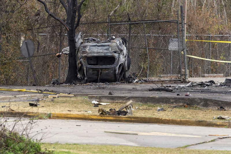A view of a damaged vehicle near the site of a plane crash after a small plane crashed into the parking lot of a post office in Lafayette, La., Saturday, Dec. 28, 2019. Several people died in the crash. (Scott Clause/The Lafayette Advertiser via AP)