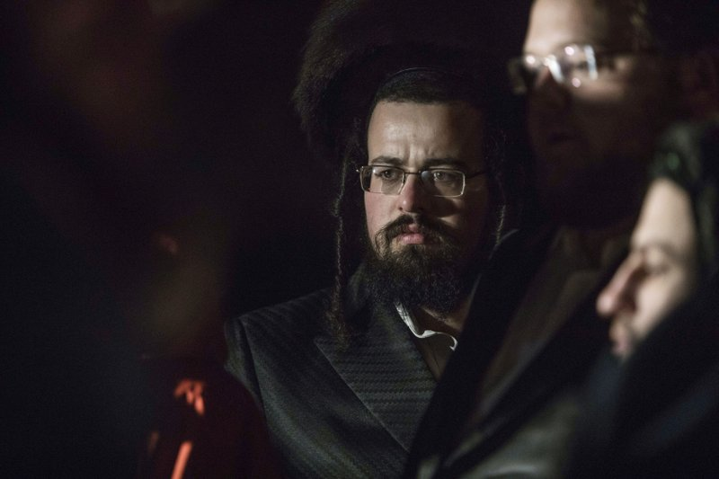 Orthodox Jewish gather on a street in Monsey, N.Y., Sunday, Dec. 29, 2019, following a stabbing late Saturday during a Hanukkah celebration. A man attacked the celebration at a rabbi's home north of New York City late Saturday, stabbing and wounding several people before fleeing in a vehicle, police said. (AP Photo/Allyse Pulliam)