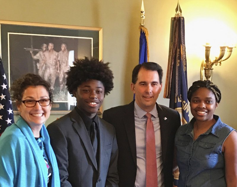 In this Aug. 23, 2017 photo provided by Durante Carr, Amy Gannon, from left, her friend AJ Carr, former Wisconsin Gov. Scott Walker and AJ's mother Dorecia Carr pose for a photo at the state Capitol in Madison, Wisconsin. Gannon, who mentored AJ Carr and became friends with his family, was aboard a helicopter that crashed Thursday, Dec. 26, 2019, in Hawaii along with her 13-year-old daughter. (Durante Carr via AP)
